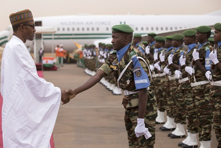 Nigerian President Muhammadu Buhari shakes hands with a Niger military officer during his arrival in Niamey, Niger, on June 3.