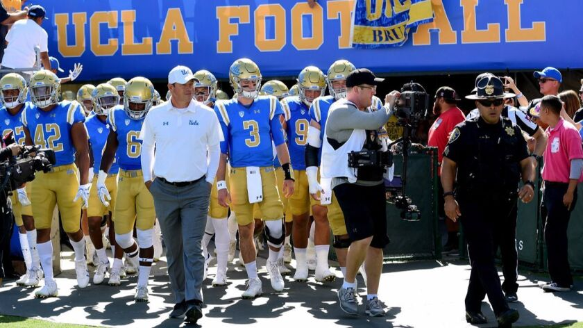 UCLA coach Jim Mora, in white shirt, lost five recruits in a span of a week.