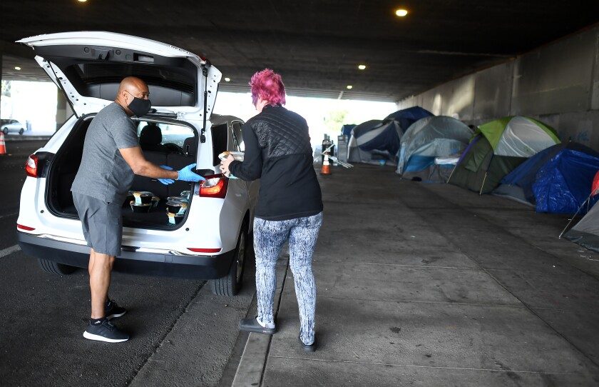 Tom Crump hands out free lunch to a homeless woman on Venice Boulevard under the 405 Freeway in Los Angeles on May 19, 2020.