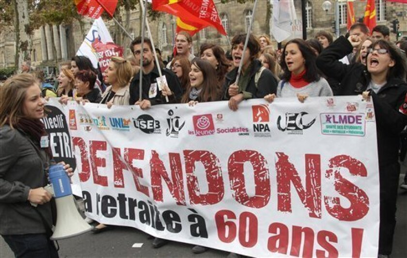 """Demonstrators hold a banner reading """"Defend our retirement age to 60"""" as they shout slogans during a workersdemonstration in Bordeaux, southwestern France, Tuesday, Oct.19, 2010. Some airliners steered clear of France and police clashed with stone-throwing youths Tuesday as a new round of nationwid"""