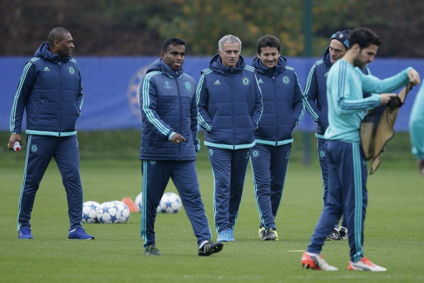 Chelsea Manager Jose Mourinho, centre, walk with his coaching staff, as Cesc Fabregas, stands in the foreground,  during a training session at their training ground in Cobham, England, Tuesday Nov. 3, 2015. Chelsea will play Dynamo Kyiv in a Group G match on Wednesday. (AP Photo/Tim Ireland)