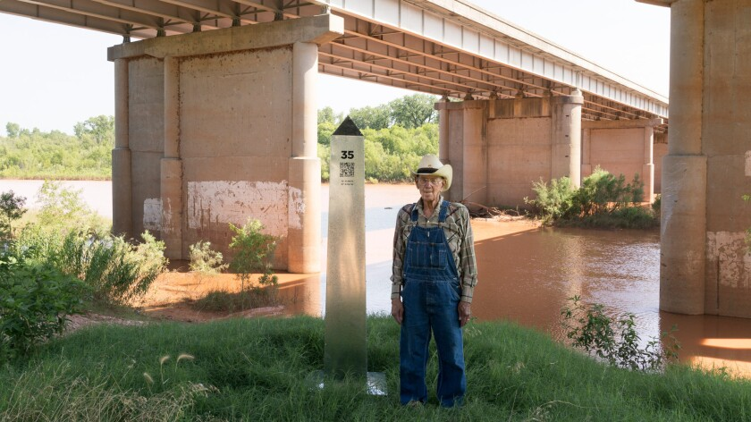 George Gilbreathe, whose father helped build this bridge over the Red River near Gainesville, Texas, stands next to a border monument.
