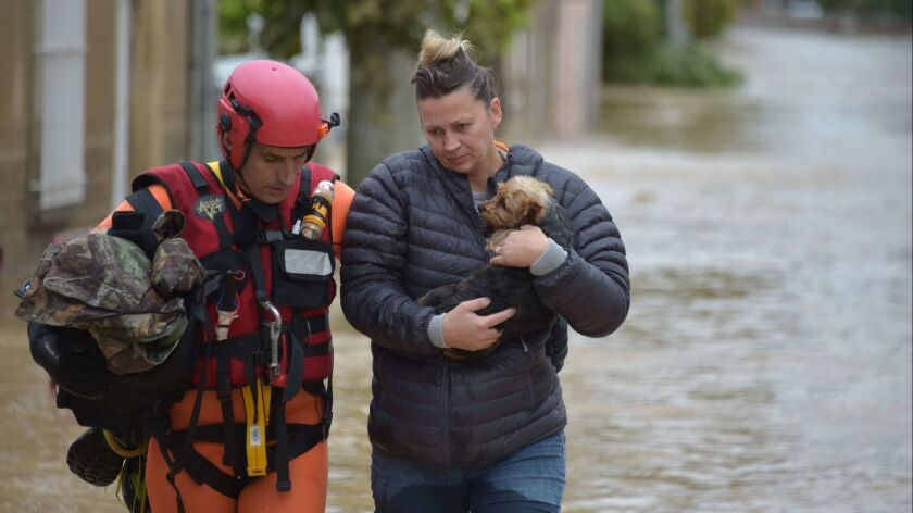 A rescuer helps a resident holding a dog following heavy rains that saw rivers bursting banks on Oct. 15 in Trebes, France.