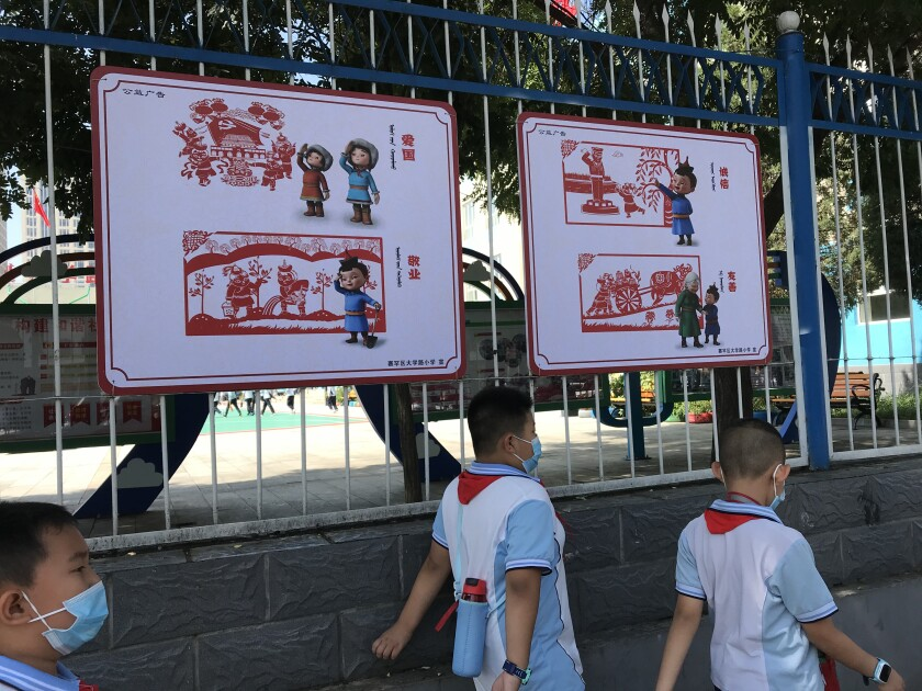 """Elementary school students in Hohhot walk past a bilingual sign promoting patriotism and other """"Chinese values."""""""
