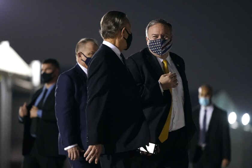 Secretary of State Mike Pompeo, center right, speaks with U.S. Ambassador to the United Arab Emirates John Rakolta before boarding a plane at Al Bateen Executive Airport in Abu Dhabi, United Arab Emirates, Sunday, Nov. 22, 2020. Pompeo is en route to Saudi Arabia. (AP Photo/Patrick Semansky, Pool)