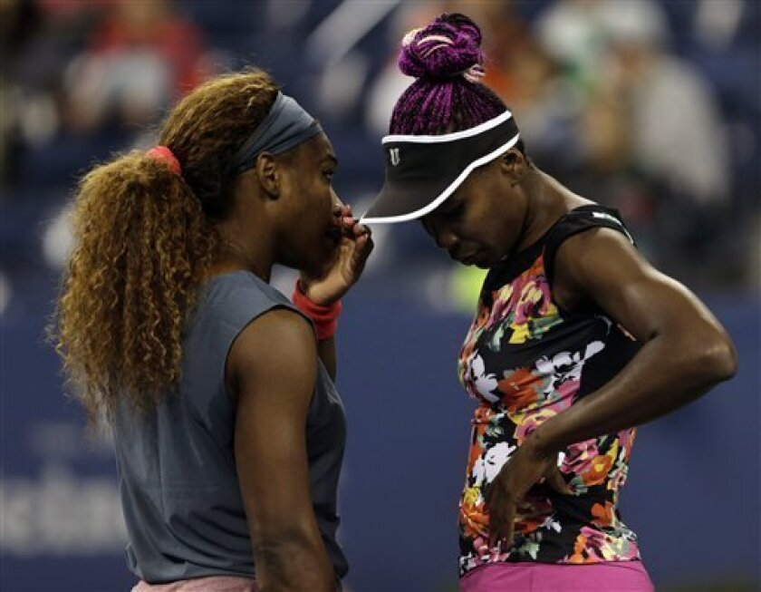 Serena Williams, left, talks with Venus Williams during their women's doubles semifinal match against Lucie Hradecka, of the Czech Republic, and Andrea Hlavackova, of the Czech Republic, at the 2013 U.S. Open tennis tournament, Friday, Sept. 6, 2013, in New York. (AP Photo/Charles Krupa)