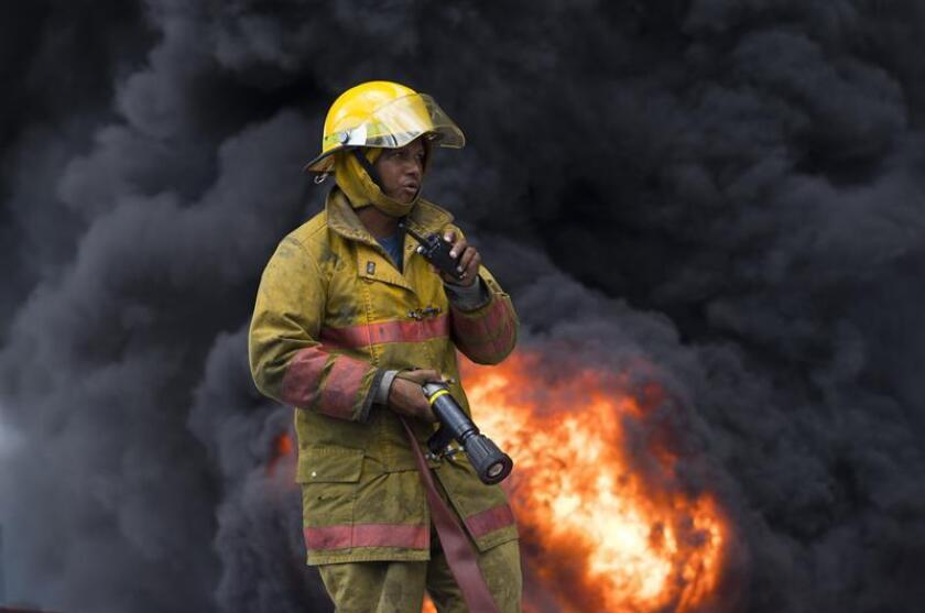 A firefighter works to control a fire resulting from an explosion a plastics factory in Santo Domingo on Dec. 5, 2018, a blast in which at least 3 people died and 44 were injured. EFE-EPA/Orlando Barria