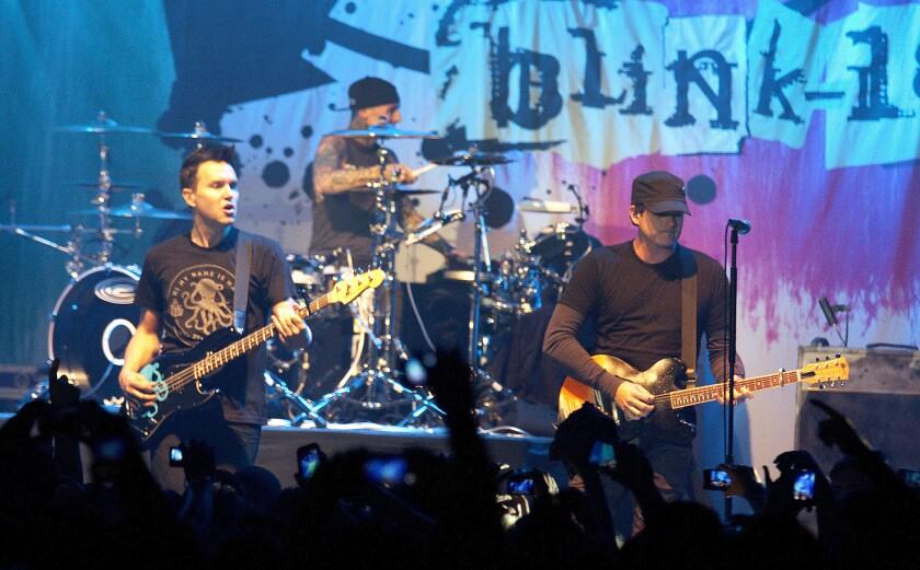 Mark Hoppus, left, Travis Barker and Tom DeLonge of Blink-182 perform at the Hollywood Palladium in 2013.