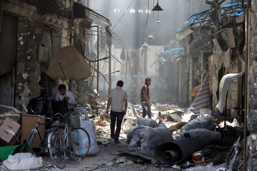 Residents of the Old City of Homs inspect their destroyed neighborhood.