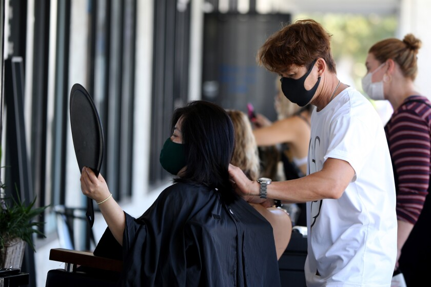 Travis Vu finishes cutting the hair of client Thuy Ngo outside TravisVu the Salon in Fountain Valley