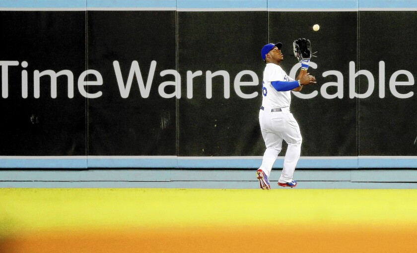 Dodgers outfielder Yasiel Puig makes a catch at Dodger Stadium this month during a game against the Angels. Most Dodgers fans have been unable to watch the team play on TV because of a pay dispute between Time Warner Cable and other pay-TV operators.