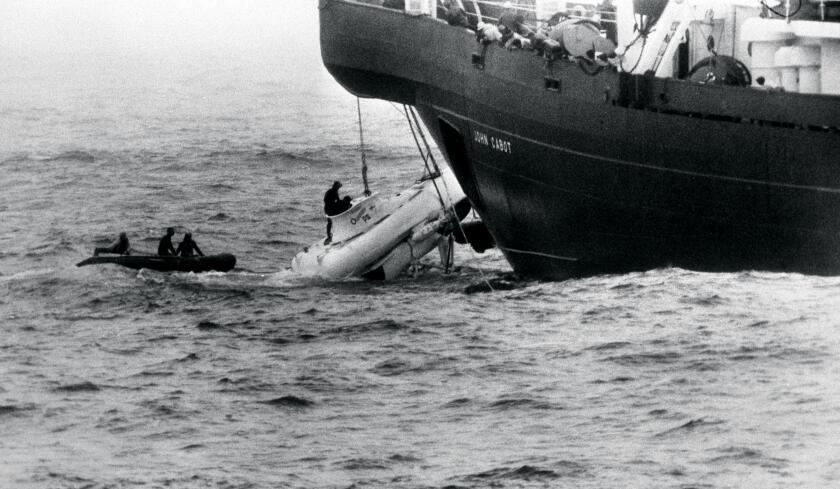 A ship hoists a small submarine out of the water
