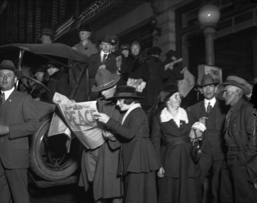 Nov. 11, 1918: A copy of the Los Angeles Times is read by members of a crowd celebrating the end of World War I.
