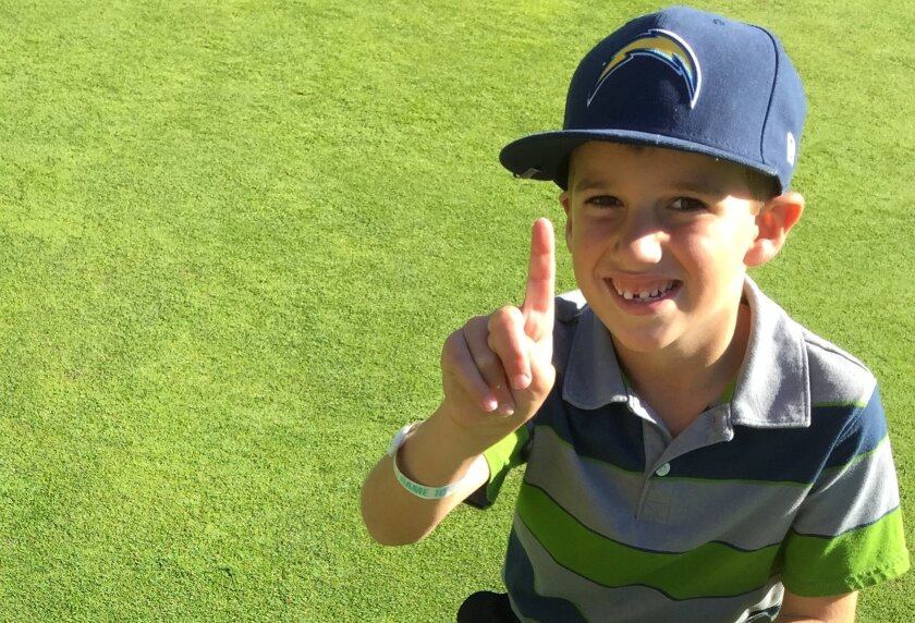 Thomas Browning, 6, of Carlsbad, poses as he prepares to pick up the ball from the hole-in-one he scored on the Sycuan Resort Pine Glen Course.