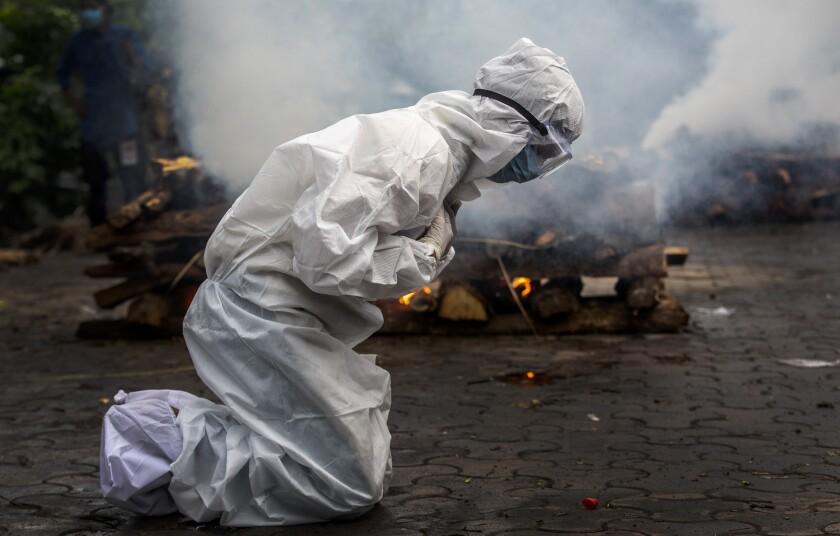Woman praying before funeral pyre
