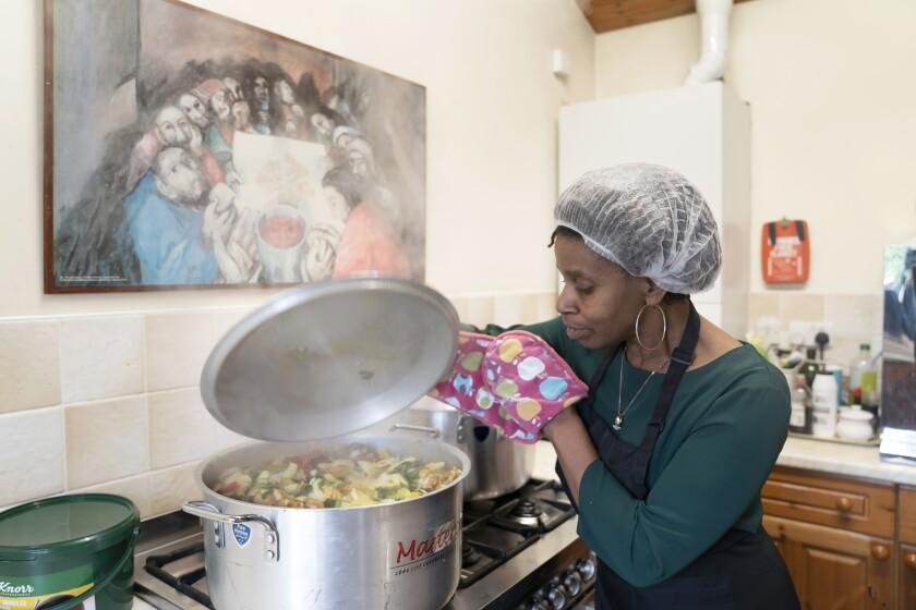 Chief coordinator Glenda Andrew checks the pot as she prepares West Indian meals with members of the Preston Windrush Covid Response team, at the Xaverian Sanctuary, in Preston, England, Friday Feb. 19, 2021. Once a week they distribute meals to people in Preston and surrounding communities in northwestern England that have recorded some of the U.K.'s highest coronavirus infection rates. The meal program grew out of Andrew's work with Preston Windrush Generation & Descendants, a group organized to fight for the rights of early immigrants from the Caribbean and other former British colonies who found themselves threatened with deportation in recent years. (AP Photo/Jon Super)