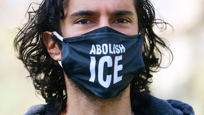 "Activist wears an ""Abolish ICE"" facemask."