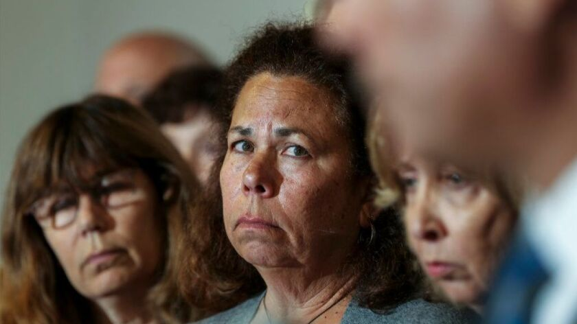Sheryl Tidus, center, flanked by other family members, appears at a news conference to promote a reward in the killing of her husband, Jeffrey Tidus, in 2009.