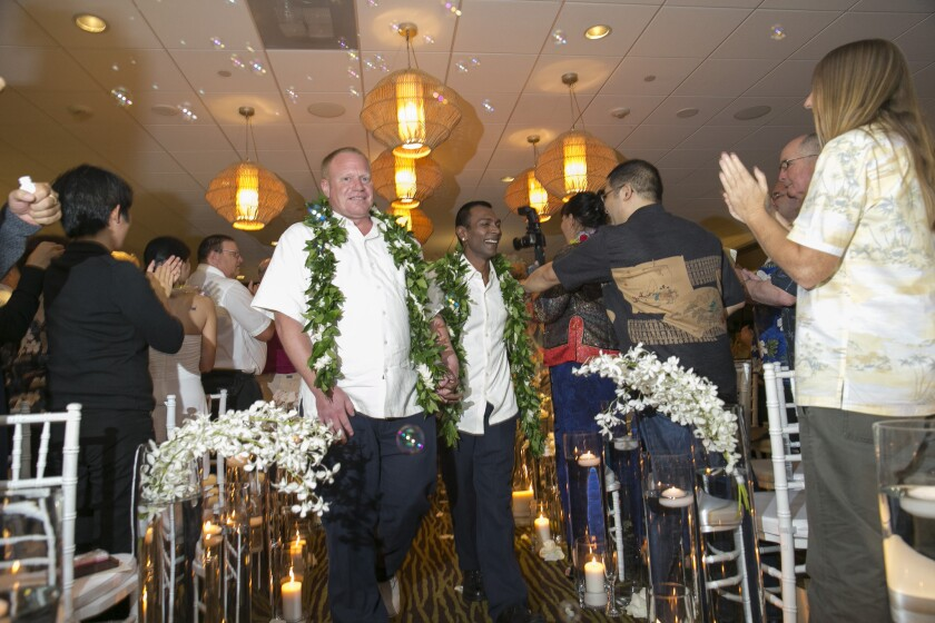 Guests applaud Shaun Campbell, left, and Tony Singh after their wedding at the Sheraton Waikiki in Honolulu.
