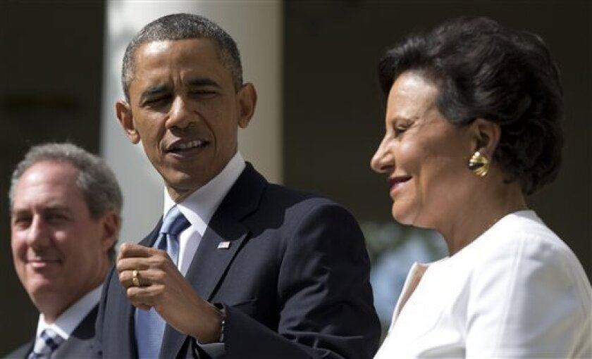 President Barack Obama looks to longtime fundraiser and philanthropist Penny Pritzker, right, in the Rose Garden of the White House in Washington, Thursday, May 2, 2013, where he announced that he will nominate Pritzker to run the Commerce Department and economic adviser Michael Froman, left, as the next U.S. Trade Representative. (AP Photo/Carolyn Kaster)