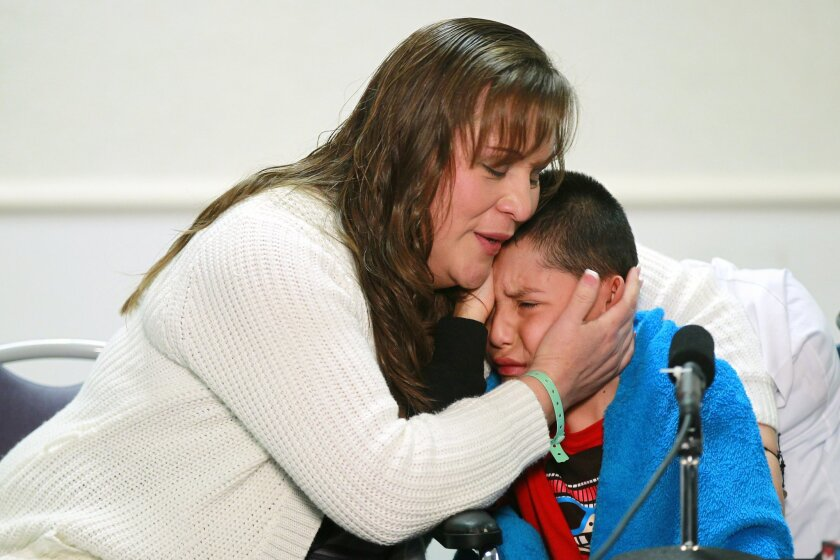 Eric Montaño, 11, gets a hug from his mother Alma Mundo after he thanked his doctors at a news conference at Rady Children's Hospital. Eric received the first pediatric heart transplant in San Diego history last week.