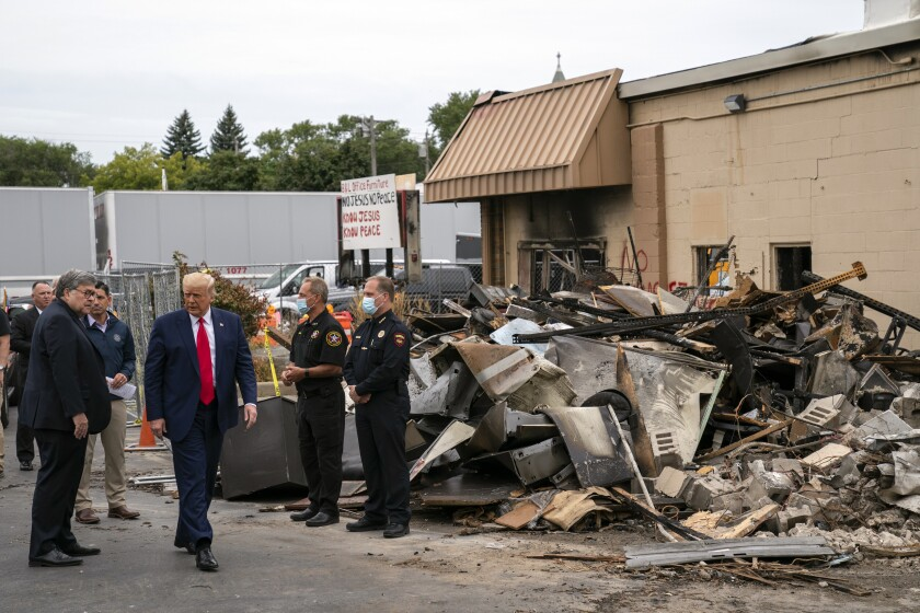 Atty. Gen. William Barr and President Trump on Tuesday tour a block in Kenosha, Wis., that was damaged during demonstrations.