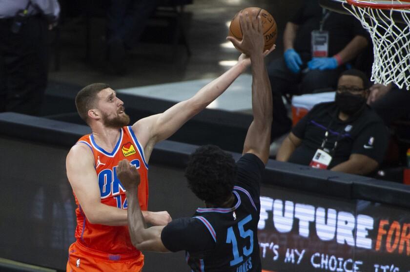 Damian Jones, pívot de los Kings de Sacramento, tapa un disparo de Svi Mykhailiuk, del Thunder de Oklahoma City, el martes 11 de mayo de 2021 (AP Foto/Randall Benton)