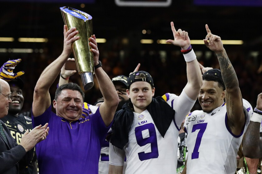 Louisiana State coach Ed Orgeron holds the trophy beside quarterback Joe Burrow, center, and safety Grant Delpit after beating Clemson in the College Football Playoff championship game on Monday in New Orleans.