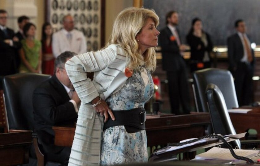 State Sen. Wendy Davis dons a back support belt given to her by colleagues during her seventh hour of filibustering during the final day of the legislative special session, as the Texas Senate considers an abortion bill in Austin.