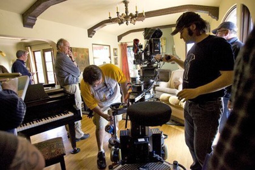 During a break at a home on Zola Street, camera angles got adjusted and director Herzog (hand on chin) surveyed the environment. The company filmed around San Diego for nearly a month. (Nelvin C. Cepeda / Union-Tribune)