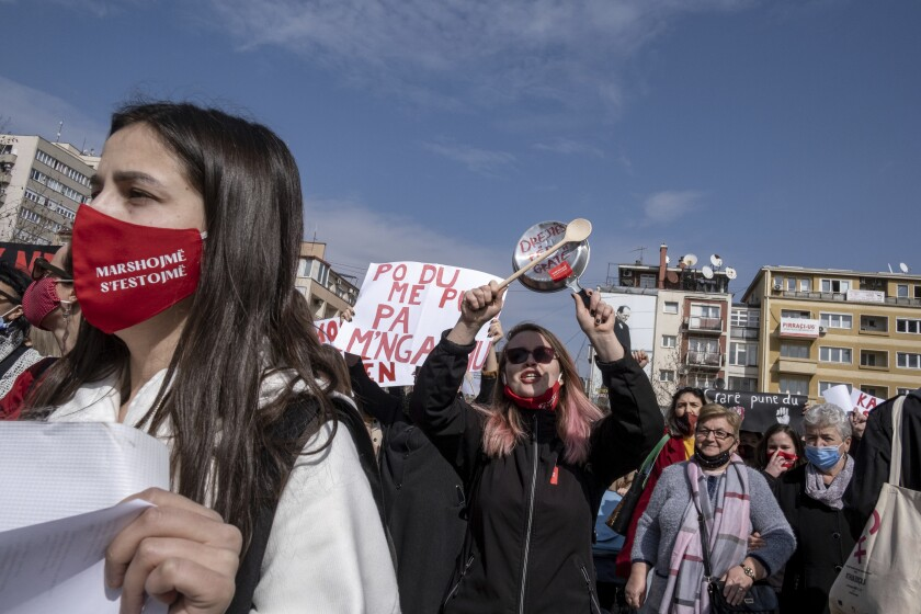 A woman bangs together kitchen utensils as she participates in a rally to ask for more respect for women's rights, in the Kosovo capital Pristina on Monday, March 8, 2021, marking International Women's Day. Participants held banners, hit kitchen utensils causing cracking sounds, to protest against the home violence which is a main complaint in a patriarchal society with hundreds of cases registered at police every year. (AP Photo/Visar Kryeziu)