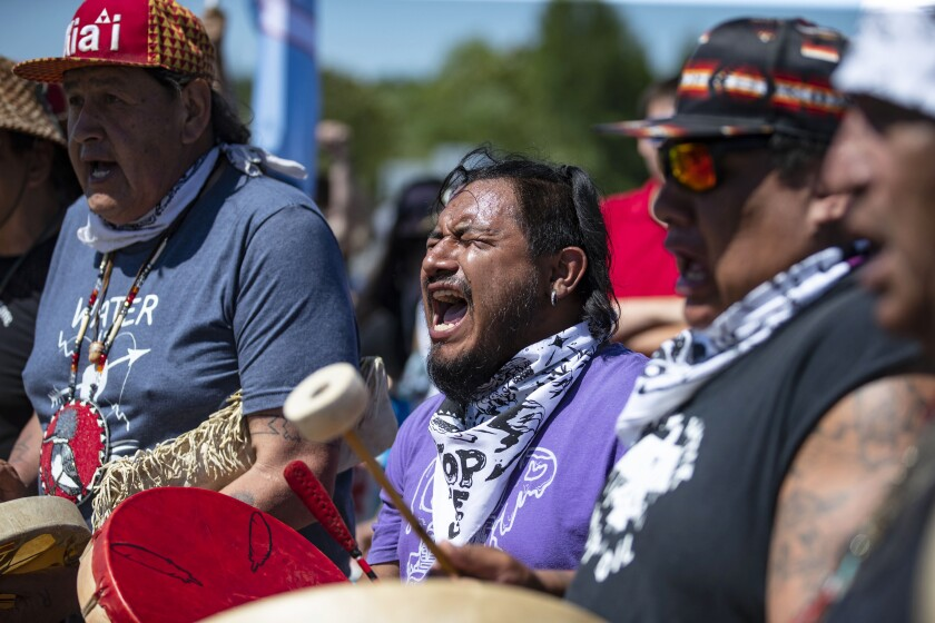 """Jesse Barrientez, aka Red Feather, center, plays the drums and sings tribal songs with other Indigenous people during a march, on Monday, June 7, 2021, in Clearwater County, Minn. More than 2,000 Indigenous leaders and """"water protectors"""" gathered in Clearwater County from around the country to protest the construction of Enbridge Line 3. The day started with a prayer circle and moved on to a march to the Mississippi headwaters where the oil pipeline is proposed to be built. (Alex Kormann/Star Tribune via AP)"""