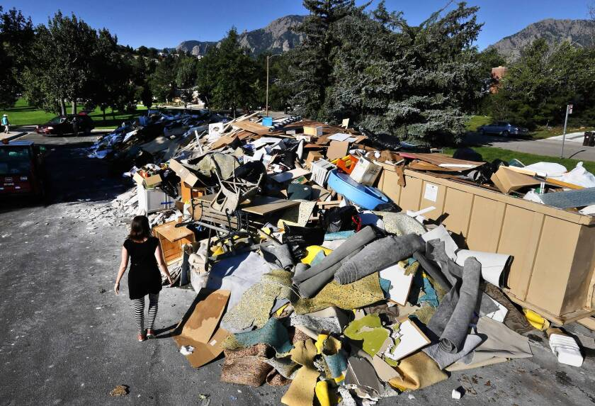 A woman looks for wood she can salvage after flooding in Boulder, Colo. Officials say damage in the city was much less than it could have been because of flood protection projects put in place since previous disasters.