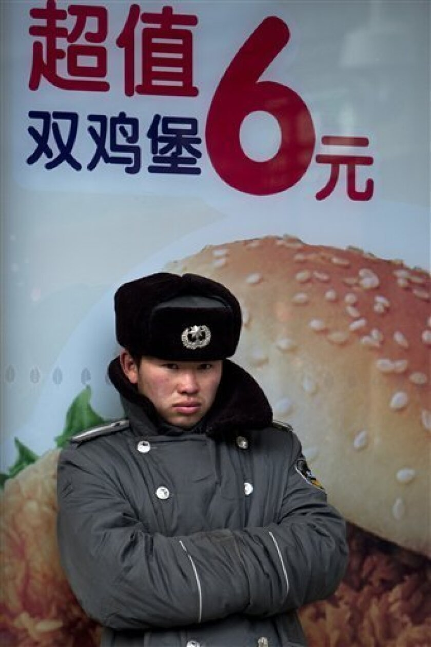 A security guard stands in front of a hamburger advertisement outside a fast food restaurant in Beijing, China, Thursday, Feb. 9, 2012. China's inflation rebounded in January as food prices soared, renewing pressure on the communist government to control surging living costs while it tries to boost slowing economic growth. (AP Photo/Alexander F. Yuan)