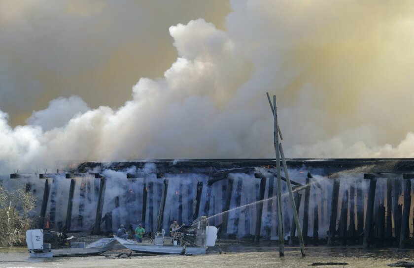 A fire burns on a train trestle parallel to Interstate 10 near the Bonnet Carre Spillway, west of New Orleans on Saturday, Feb. 13, 2016. A CN Railway spokesman says it typically carries four to eight freight trains a day, plus one passenger train in each direction. (Brett Duke/NOLA.com The Times-P