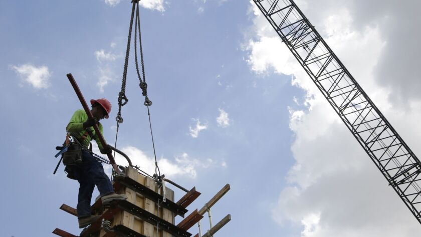 FILE- In this June 20, 2018 photo, a member of a construction team works on the site of Gables Stati