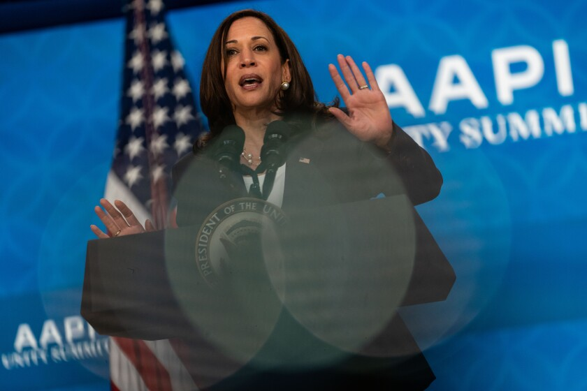 Vice President Kamala Harris speaks at a lectern and raises her hands.