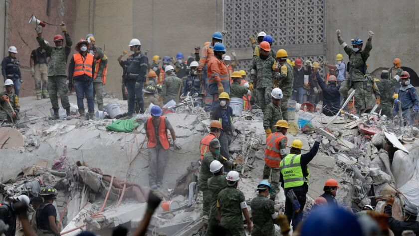 Rescue workers search for survivors, some holding their arms up as a sign to maintain silence, at an