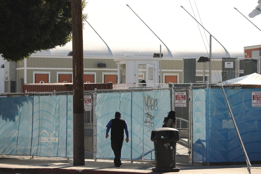 A person walks along a city sidewalk past a chain-link fence lined with blue plastic sheeting