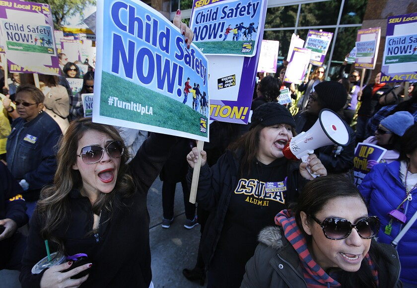 Natalie Guerra, left, and Veronica Luna (with bullhorn), both emergency response investigators for the Department of Children and Family Services, protest with other striking Los Angeles County children's social workers outside the El Monte field office of L.A. County Supervisor Gloria Molina over their caseloads.