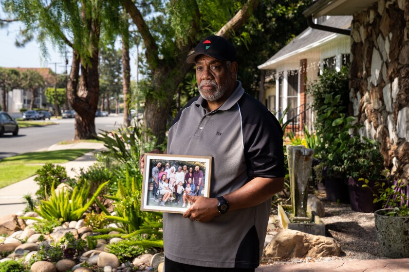 Tony Wafford, with a photo of extended family members, outside his home in Inglewood.