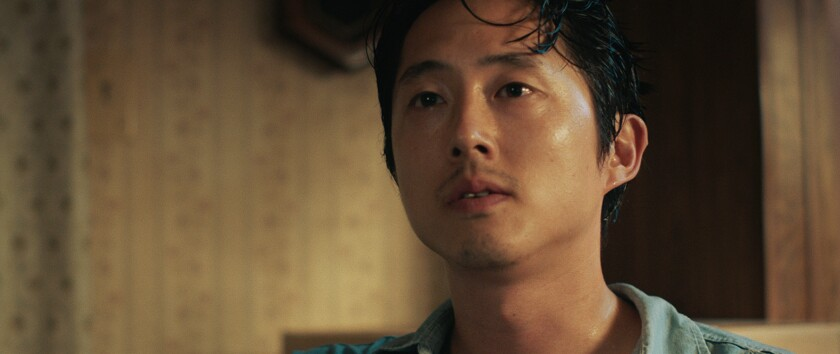 Steven Yeun is looking up at someone, his face blank. There is a patterned wallpaper behind him.