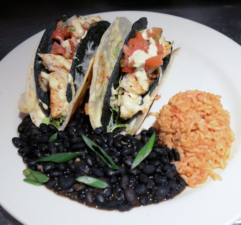 The Cajun Fish Tacos are blackened with Cajun spices in a blue corn tortilla that is wrapped in a flour tortilla. They are garnished with pepper jack cheese, lettuce, pico de gallo and Cajun remoulade, and served with sides of Red Ale rice and black beans.