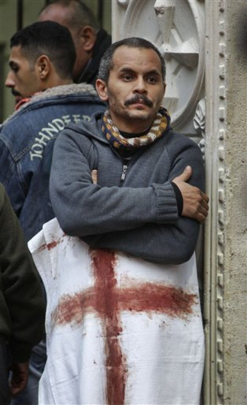 An Egyptian Copt observes the scene, wrapped in a sheet on which a Christian cross has been painted in blood, outside the Coptic Christian Saints Church in the Mediterranean port city of Alexandria, Egypt, Saturday, Jan. 1, 2011. A car exploded in front of the church early Saturday as worshippers emerged from a New Year's Mass, killing at least 21 people according to officials, and sparking clashes between Christians and Muslims, a sign of the sectarian anger that has been arising with greater frequency in Egypt. (AP Photo/Ben Curtis)