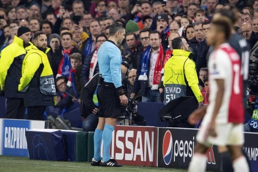 El árbitro Damir Skomina mira imágenes en el VAR luego de la jugada de gol de Nicolás Tagliafico del Ajax durante el partido de ida por los octavos de final de la Liga de Campeones de la UEFA entre el Ajax Amsterdam y el Real Madrid, este miércoles, en Amsterdam (Holanda). EFE