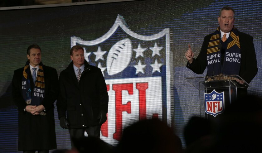 New York City Mayor Bill de Blasio, right, speaks while NFL comissioner Roger Goodell, center, and New York Gov. Andrew Cuomo, left, look on during a ceremony unveiling the Roman numerals for Super Bowl XLVIII on Super Bowl Boulevard Wednesday, Jan. 29, 2014, in New York. The Seattle Seahawks are scheduled to play the Denver Broncos in the NFL Super Bowl XLVIII football game on Sunday, Feb. 2, in East Rutherford, N.J. (AP Photo/Charlie Riedel)
