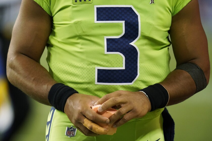 Seattle Seahawks quarterback Russell Wilson holds a sponge near his taped injured finger during the fourth quarter of an NFL football game against the Los Angeles Rams, Thursday, Oct. 7, 2021, in Seattle. Wilson left the game after the injury and the Rams won 26-17. (AP Photo/Elaine Thompson)