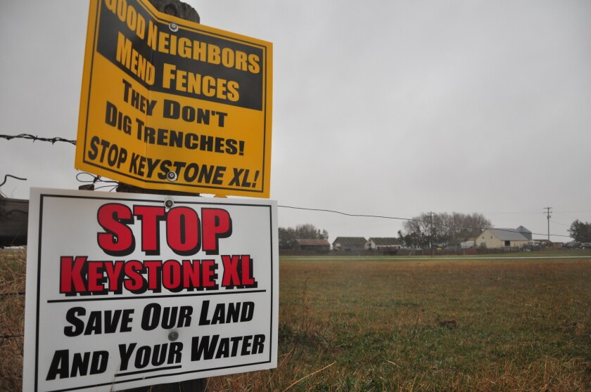 Signs are attached to a fence on the property of Jim Tarnick, a Nebraska farmer opposed to the Keystone XL pipeline project.