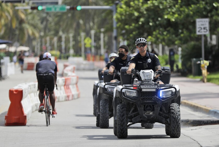 Police officers riding all terrain vehicles patrol Miami Beach, Florida's famed Ocean Drive on South Beach, July 4, 2020. The Fourth of July holiday weekend began Saturday with some sobering numbers in the Sunshine State: Florida logged a record number of people testing positive for the coronavirus. (AP Photo/Wilfredo Lee)