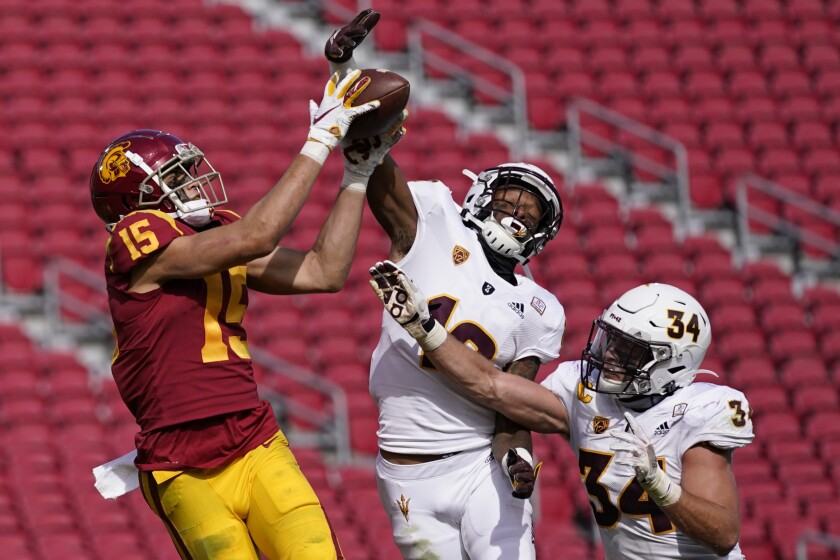 CORRECTS TO SECOND HALF, NOT FIRST HALF - Southern California wide receiver Drake London (15) catches a pass in the end zone for a touchdown as Arizona State defensive back Kejuan Markham (12) and linebacker Kyle Soelle (34) defend during the second half of an NCAA football game Saturday, Nov. 7, 2020, in Los Angeles. USC won 28-27. (AP Photo/Ashley Landis)